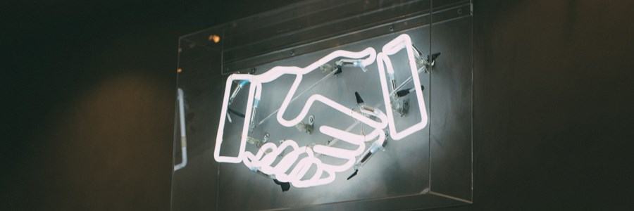 Neon sign depicting 2 hands shaking each other